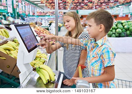 Boy And Girl Buying Bananas In Shop