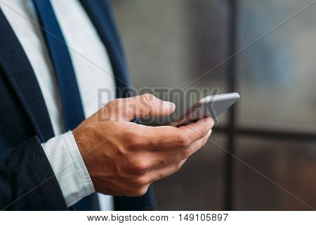 Close up of male hand holding smartphone. Business and telephone, communication, modern technology concept.