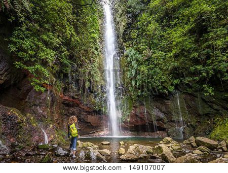 Woman tourist is standing next to the big waterfall at levada 25 fountains in Rabacal, Madeira island, Portugal. Horizontal photo.