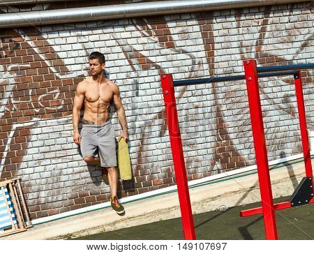 Bodybuilder resting at outdoor training ground, leaning against brick wall.