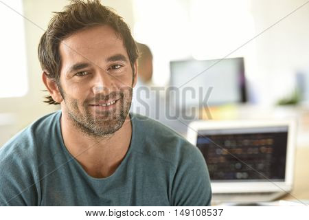 Portrait of cheerful man in office working on laptop