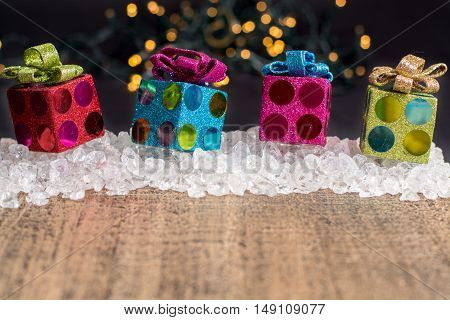 Christmas decoration colorful gift boxes on chrystal ice and golden wooden plank