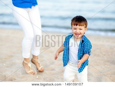 Boy run on the beach and have fun on a bright sunny day