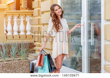 happy young caucasian woman with shopping bags outdoor