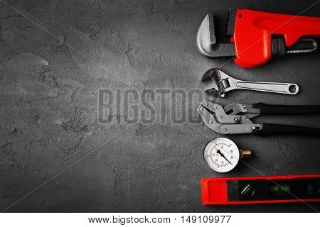 Plumber tools on concrete structure background