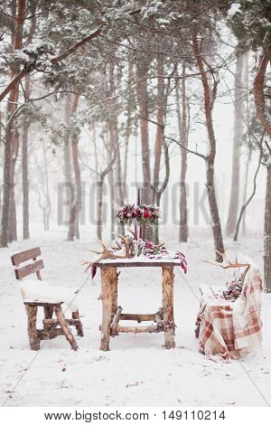 Table Made Of Pine In Snowbound Forest In Winter With Red Wedding Table Setting. Winter Wedding Conc
