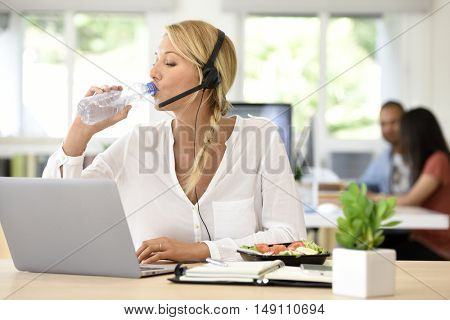 Busy customer service manager eating lunch in office