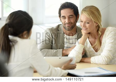 Cheerful married couple meeting financial adviser