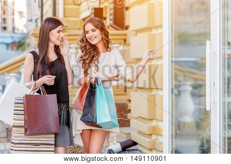 happy young caucasian women with shopping bags outdoor