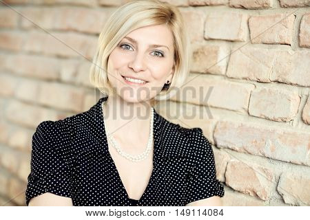 Closeup portrait of happy blonde woman smiling, looking at camera.