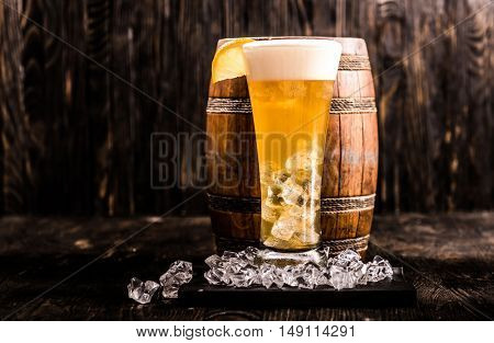 little barrel and glass of light golden beer with ice and lemon, closeup
