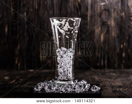 used empty glass with ice and beer foam on dark wooden background