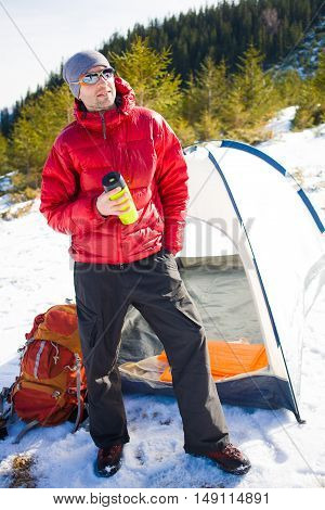 Man With A Mug And Stands Near Tents.