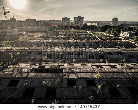 old abandoned rooof with window holes and view of town, aerial photo at sunset