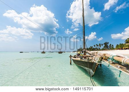 wooden boat anchored on the African shore in clear ocean water