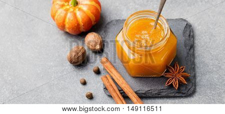 Pumpkin confiture, jam sauce with spices on stone table Copy space