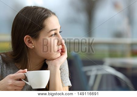 Pensive woman holding a coffee cup looking away in a restaurant terrace in a rainy day