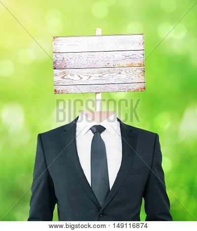 Young businessman body with wooden signboard instead of head on green background. Mock up