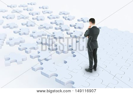 Thoughtful businessman standing on abstract white puzzle road on light background. Success concept. 3D Rendering