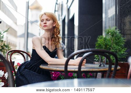 young woman in black dress at table in cafes on street
