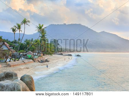 Foggy morning Samui beach with rocks on foreground