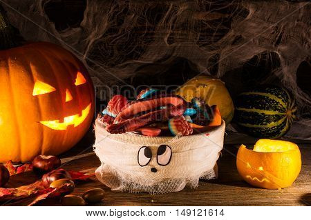 Halloween pumpkin head jack lantern orange scary lantern and mummy with sweets looks like brain on wooden background in candle light. halloween decoration