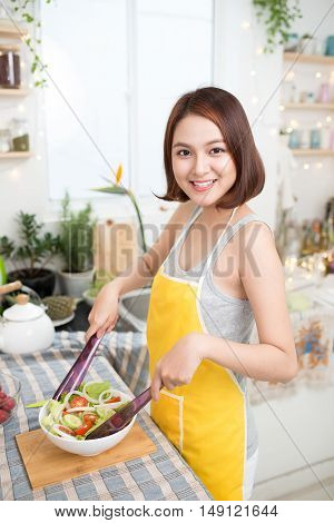 Young asian woman making salad in kitchen smiling and laughing happy at home.