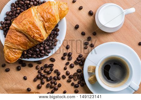 Breakfast coffee - cup, sugar, milk jug and croissant with coffee beans on wooden background. Top view.