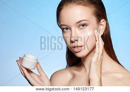 Beauty portrait of an attractive girl who smears on the face cream from the jar that holds in the hand.