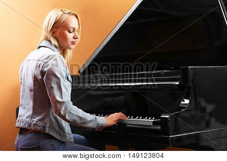 Young woman playing piano in recording studio