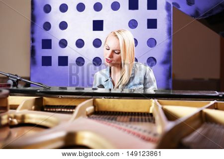 Young woman playing piano and singing in recording studio