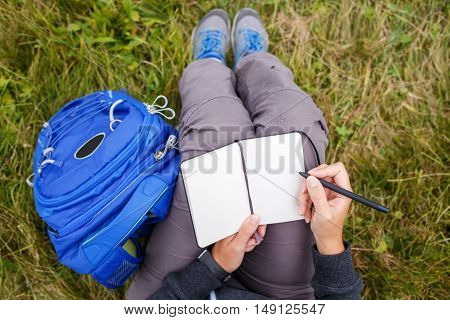 Woman Sitting On Grass And Writing Into Notebook.