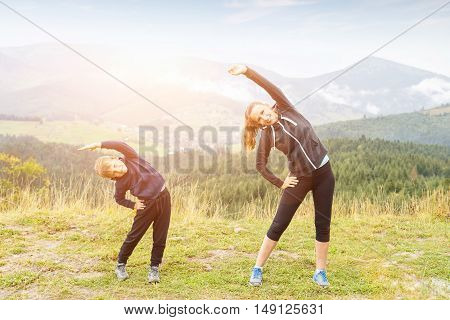 Mother and son doing stretching at the mountain outdoors morning