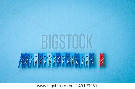 Little colorful clothes pins on a blue background