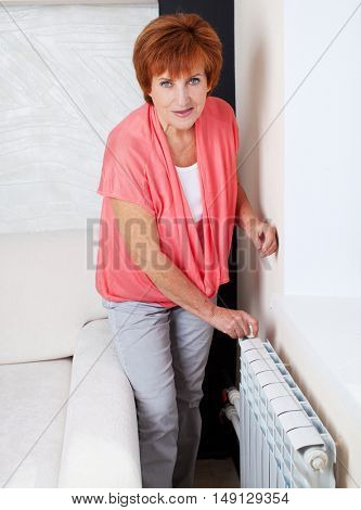 Woman controls the temperature of the radiator at home