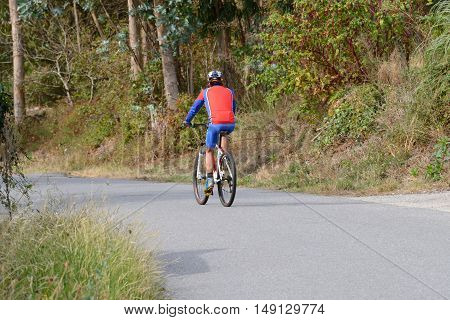 image of a cyclist on forest path