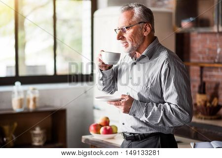 Morning coffee. Attractive old male having breakfast before going to his work