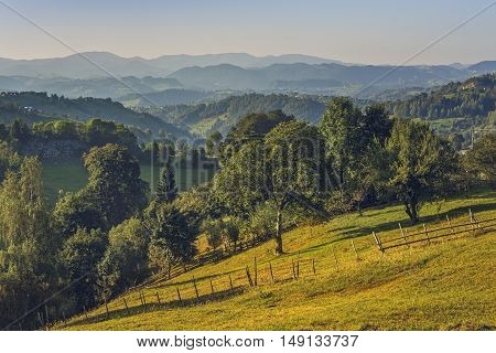 Picturesque Romanian rural scenery in Magura village Bran-Rucar pass Romania. Warm summer morning light over Transylvanian green dales. Scenic Romanian travel destinations.