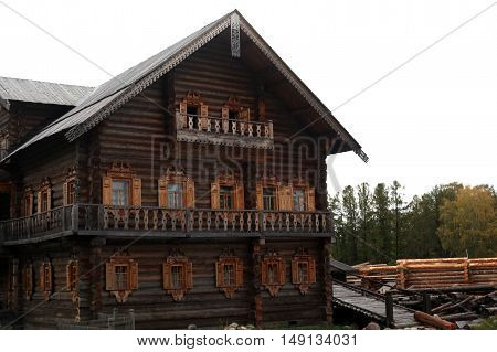 Russian wooden house decorated with carved windows, facade, roof ridge. Traditional architecture of the Russian countryside. Russia.