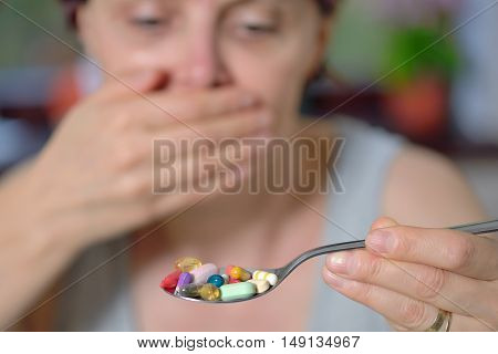 unwanted take pills woman holding spoon with pills