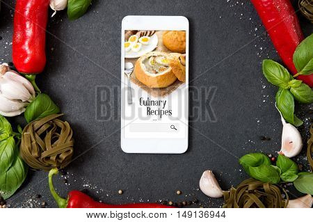Smartphone with culinary recipes application lying on stone counter and surrounded by fresh herbs and hot spices