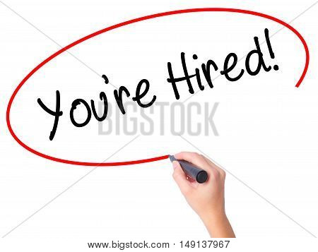 Women Hand Writing You're Hired! With Black Marker On Visual Screen