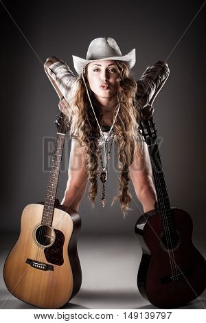 Fashion girl with guitar playing hard-rock. Picture with high contrast effect.