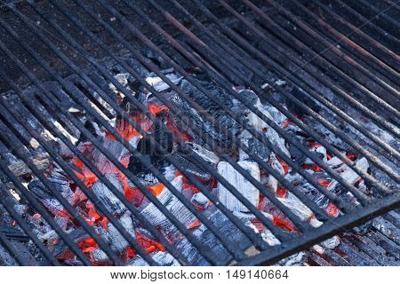 Empty barbecue grill with burning charcoal briquettes under.