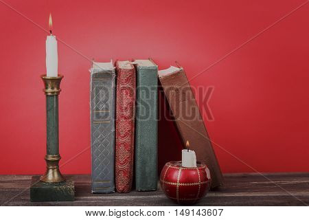 Vintage books burning candles in candlesticks on red background.