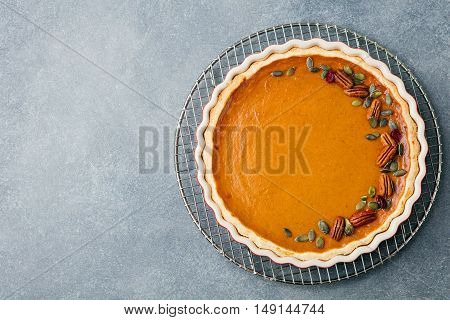 Tasty pumpkin pie, tart made for Thanksgiving day in a baking dish on a colling rack. Grey stone background. Top view Copy space