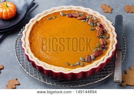 Tasty pumpkin pie, tart made for Thanksgiving day in a baking dish on a colling rack. Grey stone background.
