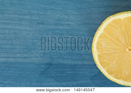 Acid and yellow fruit. Half lemon on a blue wood
