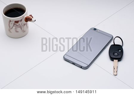 mobile phone ,car key, cup of coffee, Jack Russel dog side of coffee cup, on white table