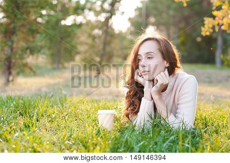 Beautiful girl 20-24 year old resting in park lying on green fresh grass with cup of coffee. Posing outdoors. Looking away.